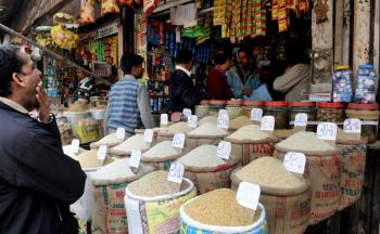 HIGH PRICES: Indian customers purchase grains from a shop at a market in New Delhi on Feb. 16. Rising food prices will put more than 40 million people in poverty if left unchecked, World Bank says. (Raveendran/AFP/Getty Images)