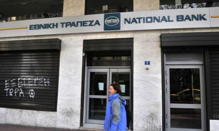 A woman passes by a National Bank branch in Greece last year. National Bank was the largest of four Greek banks to get part of a US$23 billion cash infusion from the European Financial Stability Fund, announced Monday. (Louisa Gouliamaki/AFP/Getty Images)