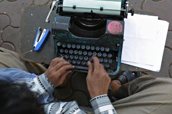 Professional typist Purushottam Sakhare typing an affidavit on his typewriter at a sidewalk outside a city court in Mumbai on Feb. 15. (Indranil Mukherjee/AFP/Getty Images)