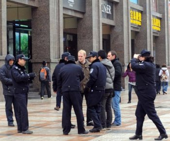 Chinese police surround a group of foreign journalists as security is ramped up, with at least 300 hundred uniformed police guarding the entrance to the Jasmine rally site, designated in an online appeal, in the Wangfujing shopping street in central Beijing on Feb 27. (AFP/Getty Images)