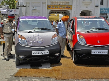 INSPECTING: Bystanders take a closer look at Tata Nano cars, billed as the 'world's cheapest car,' taking part in a road tour in Amritsar, India on June 9, 2010. (Narinder Nanu/AFP/Getty Images )