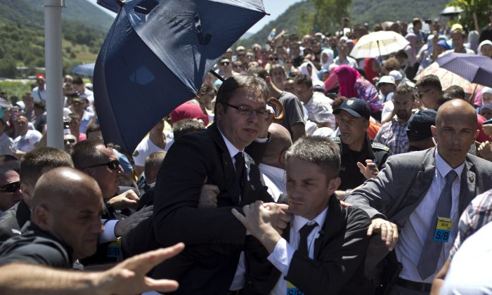 Aleksandar Vucic, Serbia's prime minister, center, is seen during a scuffle at the Potocari memorial complex near Srebrenica, 150 kilometers northeast of Sarajevo, Bosnia and Herzegovina, Saturday, July 11, 2015. Anger boiled over Saturday at a massive commemoration of the Srebrenica slaughter 20 years ago as people pelted Vucic with water bottles and other objects. (AP Photo/Marko Drobnjakovic)