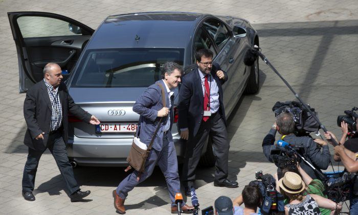 Greek Finance Minister Euclid Tsakalotos, second left, arrives for a meeting of eurozone finance ministers at the EU Lex building in Brussels on Saturday, July 11, 2015. Greece's negotiators head to Brussels on Saturday armed with their reform proposals and parliamentary backing to seek a third bailout, but with the shadow of severe dissent from governing lawmakers hanging over them. (AP Photo/Virginia Mayo)