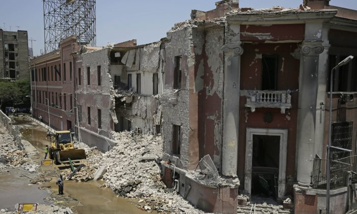 Workers clear rubble at the site of an explosion near the Italian Consulate in downtown, Cairo, Egypt, Saturday, July 11, 2015.  Italy's foreign minister vowed that his country would not be intimidated after a deadly explosion Saturday morning killed one person and heavily damaged the Italian Consulate in the Egyptian capital. (AP Photo/Thomas Hartwell)
