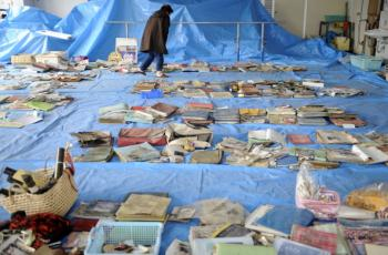 Japan: A survivor checks salvaged memorial pictures and goods on display at a corner of the town hall in Yamada town, Iwate prefecture on March 25, 2011.  (Toshifumo Kitamura/AFP/Getty Images)