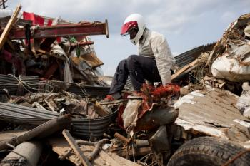 A Japanese man finds his friend's car in the tsunami debris in Rikuzentakata, Iwate prefecture, on April 2, 2011. (Yashuyoshi Chiba/AFP/Getty Images)