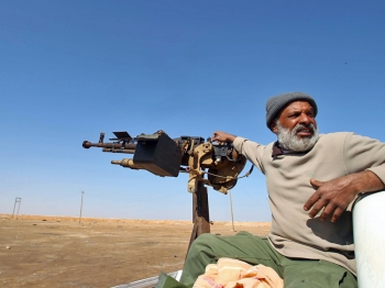 A Libyan rebel sits next to a heavy machine gun at the western gate of the eastern city of Ajdabiya, on April 12, 2011. (Marwan Naamani/AFP/Getty Images)