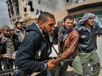 A photo taken by slain photographer Chris Hondros shows Libyan rebel fighters carrying out a comrade wounded during an effort to dislodge some ensconced government loyalist troops on April 20, 2011 in Misrata, Libya. Hondros was killed on Wednesday. (Chris Hondros/Getty Images)