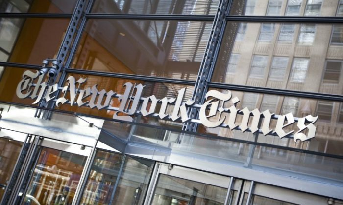 The New York Times logo is seen on the headquarters building in New York City in this file photo. The New York Times is aiming to cut 30 positions in order to shrink the size of its newsroom, citing financial challenges. (Ramin Talaie/Getty Images)