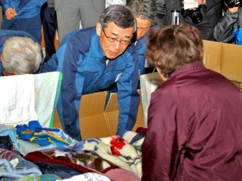 Tokyo Electric Power Co. President Masataka Shimizu (C) bows to an elderly evacuee to apologize for the accident at his company's Fukushima Daiichi nuclear plant at a shelter at Koriyama, Fukushima prefecture on April 22.(Jiji Press/AFP/Getty Images)