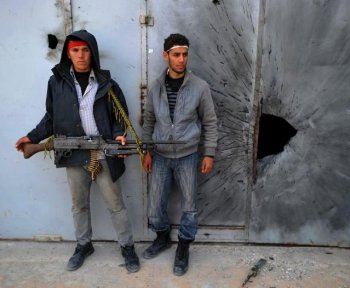 THE NEXT MOVE: Libyan rebels stand close to a building where forces loyal to leader Moammar Gadhafi are suspected to be held up in the Zwabi District of the city of Misrata on April 24.  (Christophe Simon/Getty Images )