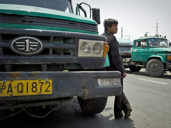A Chinese mechanic waits by a container truck to be repaired near a cargo terminal in Shanghai on April 25. (Philippe Lopez/AFP/Getty Images)