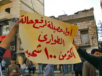 Syrians protest in the city of Banias holding up a sign that reads in Arabic: 'The first results in lifting the state of emergency is over 100 deaths' on April 26, 2011. (AFP/Getty Images)