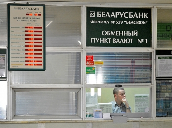 A bank worker sits inside an exchange office in Minsk, on April 27, 2011. Belarus has struggled through a deepening fiscal crisis which began last year when Russia raised the price it charges for energy.  (Viktor Drachew/Getty Images)