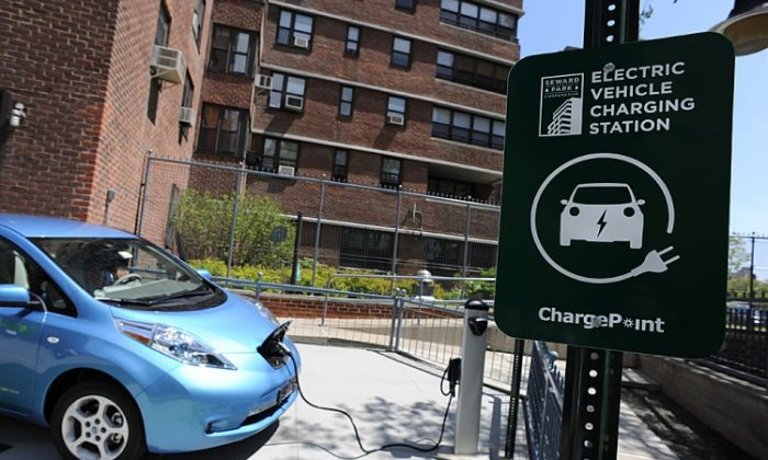 A Nissan Leaf electric vehicle (EV) is plugged into a charging station at the Seward Park Co-op apartments on Manhattan's Lower East Side, May 2011. Americans may still prefer hybrid cars to EV, but nonetheless there is a battle heating up between companies competing to install user fee-based EV charging stations in the United States. (STAN HONDA/AFP/Getty Images)