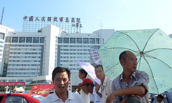 Men stand at the entrance of the 301 Military Hospital in Beijing, where top Chinese leaders often receive medical care, in July 2011. (Liu Jin/AFP/Getty Images)