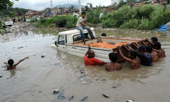 Monsoon rains in Nepal caused widespread flooding last July, 2011. A submerged jeep is pushed out of flood water near Bagmati River in Kathmandu on July 20, 2011. (Prakash Mathema/AFP/Getty Images)