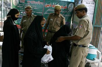Indian police check the bags of Indian Muslim women visiting the Jama Masjid mosque (Background) in New Delhi on July 27, 2008, after security was put on high alert across the country following the bomb blasts in Ahmedabad.  (Manpreet Romana/AFP/Getty Images)