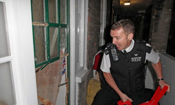 A Metropolitan police officer breaks down a door in a raid on a house in connection with the riots in London in August 2011. Extreme physical exertion can impair an officer's memory of an event, according to a new study. (Nigel Howard/AFP/Getty Images)