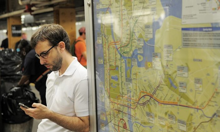 A man checks his cell phone on a subway platform in the Union Square station of the L line on September 27, 2011 in New York. (STAN HONDA/AFP/Getty Images)