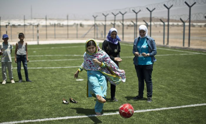 Nobel Peace Prize recipient Malala Yousafzai, 18, kicks the ball while playing soccer with Syrian refugee children during her visit to Azraq refugee camp in Jordan, Monday, July 13, 2015.  (AP Photo/Muhammed Muheisen)