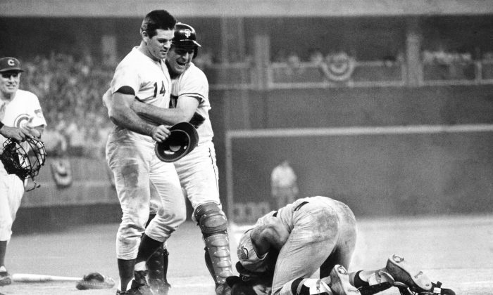 Pete Rose (L) is hugged by teammate Dick Dietz after scoring the winning run while running over  catcher Ray Fosse (R), who suffered a separated shoulder on the play. (AP Photo)