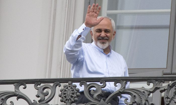 Iranian Foreign Minister Mohammad Javad Zarif waves from a balcony of the Palais Coburg Hotel where the Iran nuclear talks meetings are being held in Vienna, Austria on July 13, 2015. (Joe Klamar/AFP/Getty Images)