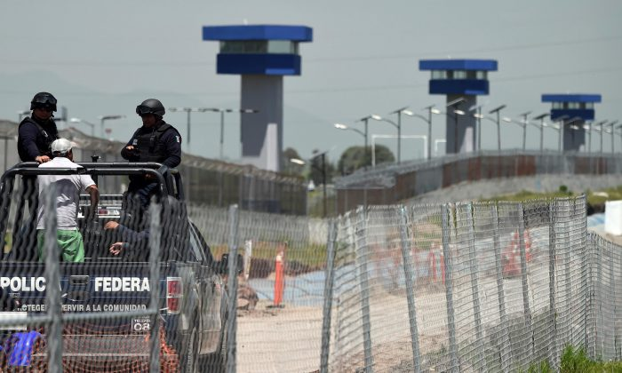 "Federal Police officers patrol the perimeter of the Altiplano prison in Almoloya de Juarez, Mexico, on July 13, 2015 a day after the government informed of the escape of drug kingpin Joaquin ""El Chapo"" Guzman from the maximum-security prison. (Alfredo Estrella/AFP/Getty Images)"