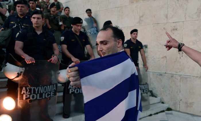 A man wrapped in a greek flag stands in front of  the stairs leading to the Greek parliament in Athens during an  anti-EU demonstration in Athens calling for a 'NO' to any agreement with the creditors on July 13, 2015. (Louisa Gouliamaki/AFP/Getty Images)