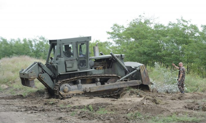 A bulldozer of the Hungarian Defence Force is used to prepare the terrain for the building of at the Hungarian-Serbian border near Morahalom, 179 kms southeast from Budapest, Monday, July 13, 2015. The fence is meant to stem the unprecedented flow of migrants, the government said Monday. (Zoltan Gergely Kelemen/MTI via AP)