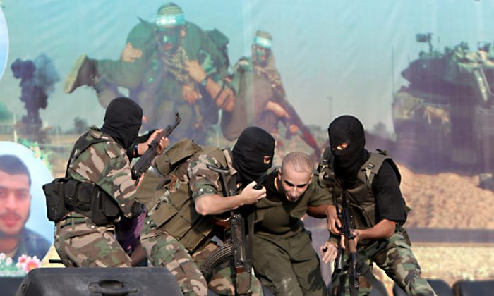"Palestinian militants with the Ezzedine Al-Qassam Brigades, the armed wing of the Islamist movement Hamas, simulate the kidnapping of Israeli soldier on Oct. 28. Hamas recently declared that computer hacking is the ""new field of resistance."" (Said Khatib/Getty Images)"