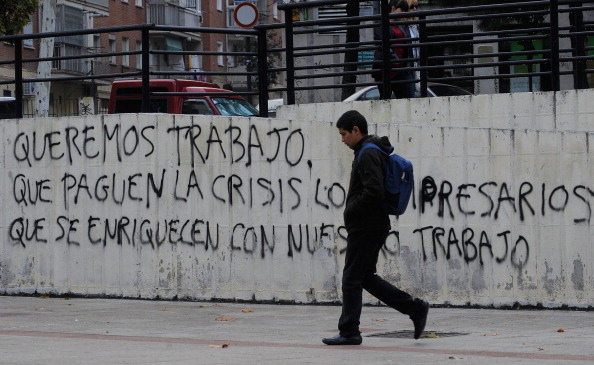 A youth walks past graffitti which reads 'We want to work, let the businessmen who have got rich from our labour pay for the crisis' on November 10, 2011 in Madrid, Spain. (Denis Doyle/Getty Images)