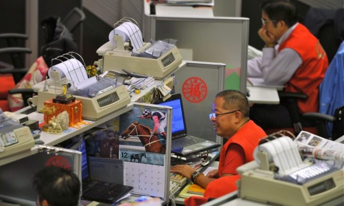 Traders sit at their desks at the Hong Kong Stock Exchange (HKEx), Dec. 15. Beginning March 5, HKEx traders had their lunch breaks shortened in an effort to boost trading volume and allow HKEx to compete with regional and global peers. (Aaron Tam/AFP/Getty Images)