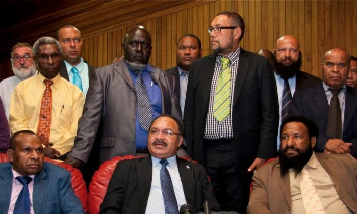 Peter O'Neill (front C) speaks at a press conference in Port Moresby on Dec. 15, 2011. (Ness Kerton/AFP/Getty Images)