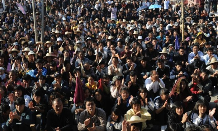 Government vehicles return to Wukan as village leader Lin Zuluan met with a senior government official to reach an agreement over illegal land grabs and the death in custody of a local leader in Wukan, Guangdong Province on Dec. 21, 2011. (Mark Ralston/AFP/Getty Images)