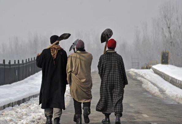 Kashmiri municipal workers walk on the banks of a Dal lake in Srinagar near Jammu on January 17, 2012.