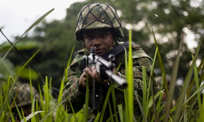 Colombian soldiers conduct a patrol across a field in a mountainous area in Miranda, Cauca department, Colombia, on January 18, 2012. The Colombian army created the Apolo joint task force with area of influence located in the southwestern department of Cauca. TF Apolo is responsible for fighting the Revolutionary Armed Forces of Colombia (FARC). (Luis Robayo/AFP/Getty Images)