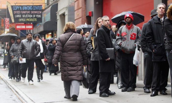 Job seekers line up to attend a job fair in Manhattan on Jan. 26. Experts suggest that corporations and the government need to create jobs that provide income for the unemployed. (Mario Tama/Getty Images)