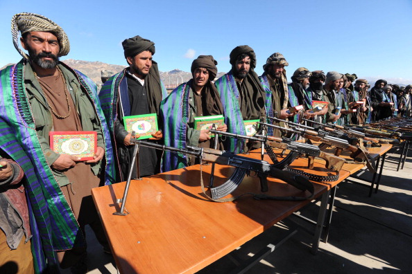 Taliban fighters stand with their weapons as they hold the Muslim holy book Koran after they joined Afghan government forces during a ceremony in Herat province on January 30, 2012. (Aref Karimi/AFP/Getty Images)