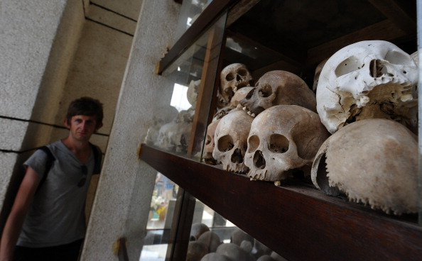 A foreign tourist walks past skulls of Khmer Rouge's victims displayed in a stupa at the site of the former killing field at Choeung Ek in the outskirts of Phnom Penh on February 2, 2012. (Hoang Dinh Nam/AFP/Getty Images)