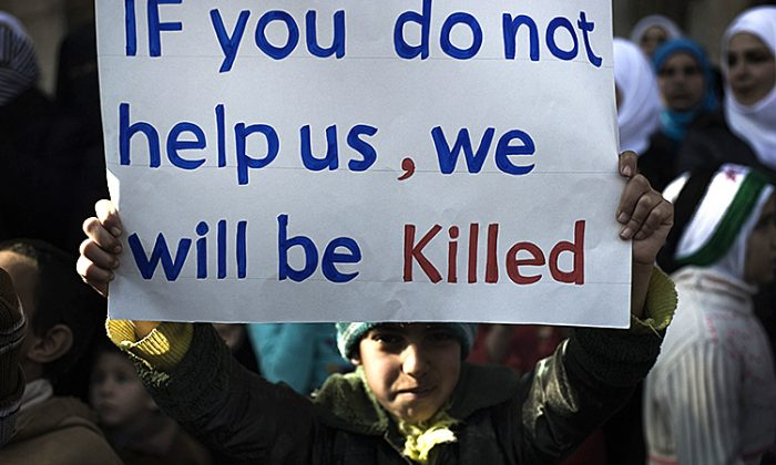A young boy holds up a sign during an anti-regime demonstration in the Syrian village of al-Qsair, 25 km southwest of the flashpoint city Homs, on February 3, 2012. At least 107 were killed across Homs on Feb. 9, the Local Coordination Committees (LCC) said. (Alessio Romenzi/AFP/Getty Images)