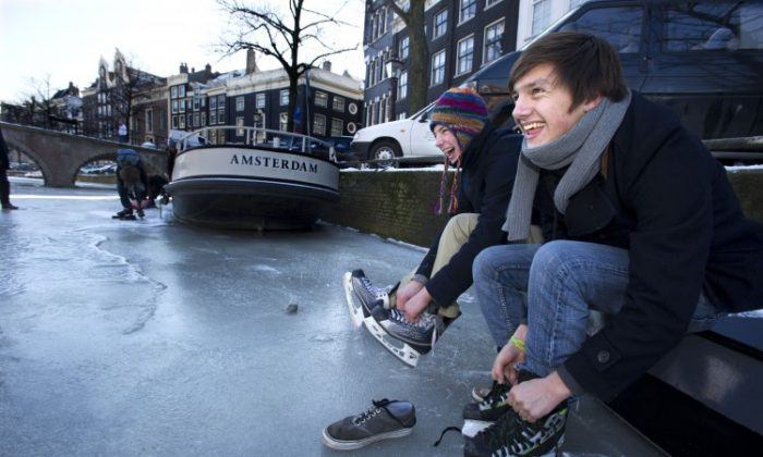 """Youth prepare to skate on a frozen canal in Amsterdam, on Feb. 6. The Netherlands famous Eleven Cities Tour on natural ice, will not go ahead for now as hoped because the ice is too thin on parts of the 125-mile """"track."""" (Evert Elzinga/AFP/Getty Images)"""