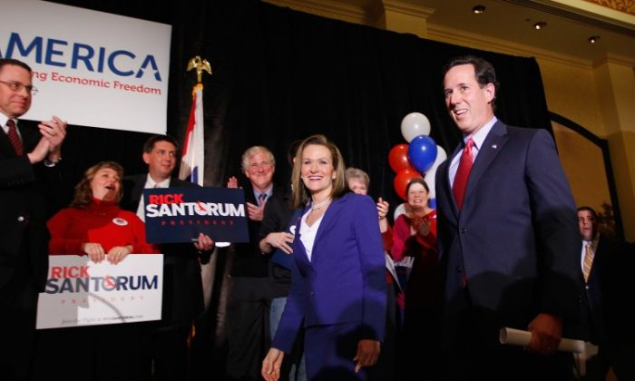 Republican presidential candidate, former Sen. Rick Santorum (R) takes the stage with his wife Karen during a primary election night party, Feb. 7, at the St. Charles Convention Center in St. Charles, Missouri. (Whitney Curtis/Getty Images)