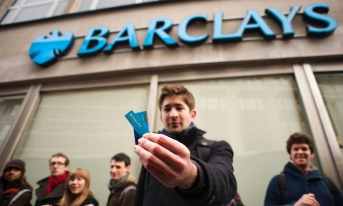 "Barclays customer George Gabriel holds the pieces of his cut-up bank card during a protest outside a branch of Barclays bank in central London on February 10, 2012. The protest was a part of the ""Move Your Money"" campaign, the stated aims of which are to try to create what they consider a better banking system through consumer power. Barclays announced a 16-percent drop in annual net profits to 3.0 billion British pounds on falling revenues at its investment arm, and also announced a one-quarter cut in its bonus pool on February 10. (Leon Neal/AFP/Getty Images)"