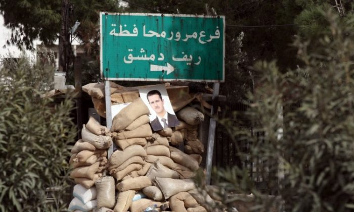 A picture of Syrian President Bashar Assad hangs on unused sand bags placed by the Syrian amry close to the city of Harasta north of Damascus on February 15, 2012. (Photo credit should read Louai Beshara/AFP/Getty Images)