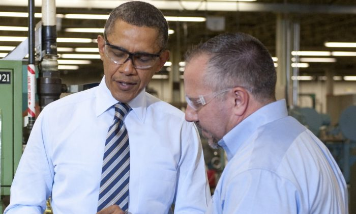 President Barack Obama (L) examines a lock at Master Lock, alongside Bob Rice (R), Master Lock Senior Vice President, in Milwaukee, Wis., on Feb. 15. (SAUL LOEB/AFP/Getty Images)