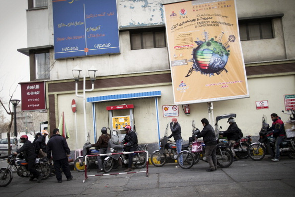 Iranians line up at a petrol station to fuel their motorcycles in central Tehran on February 19, 2012. Iran has halted its limited oil sales to France and Britain on Sunday in retaliation for a phased EU ban on Iranian oil that is yet to take full effect. (Behrouz Mehri/AFP/Getty Images)