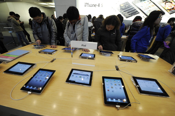 Customers look at Apple iPads at a store in Shanghai on February 22, 2012. (Peter Parks/APF/Getty Images)