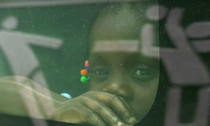 In this June 29, 2015 photo, a girl born in the Dominican Republic to Haitian parents peers through the window of a government car that will transport her and her family to the border with Haiti, in Santo Domingo, as her family returns voluntarily to their native Haiti after living in the DR several years. (AP Photo/Ezequiel Abiu Lopez)