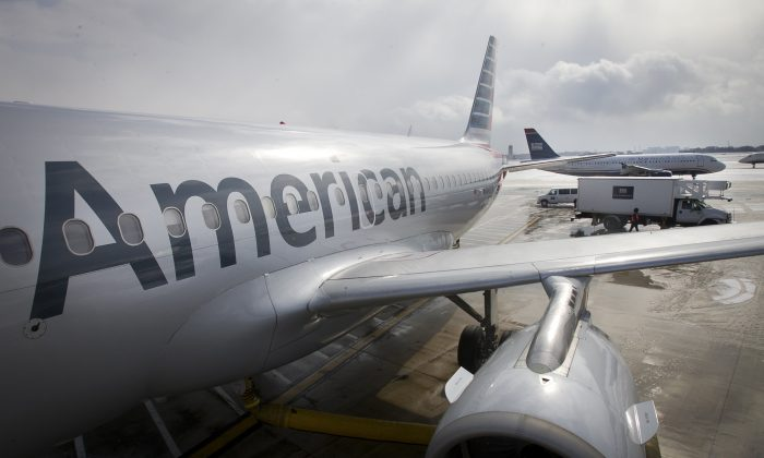 In this Feb. 26, 2014 file photo, an American Airlines Airbus A319 is parked at a gate at Philadelphia International Airport as a US Airways plane taxis in the background, in Exton, Pa. (Alejandro A. Alvarez/Philadelphia Daily News via AP)